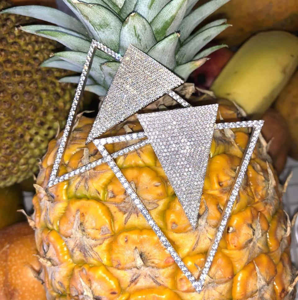 two triangle style bold earrings on a file of fruits including pineapple and banana