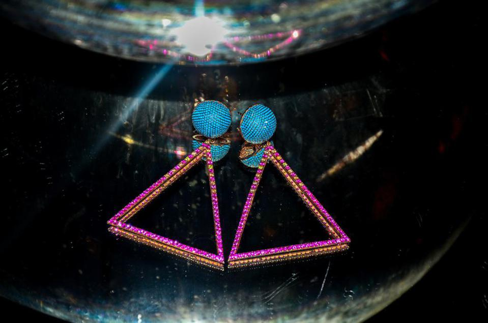 triangle shaped earrings in contrasting turquoise and bright pink diamonds on dark table