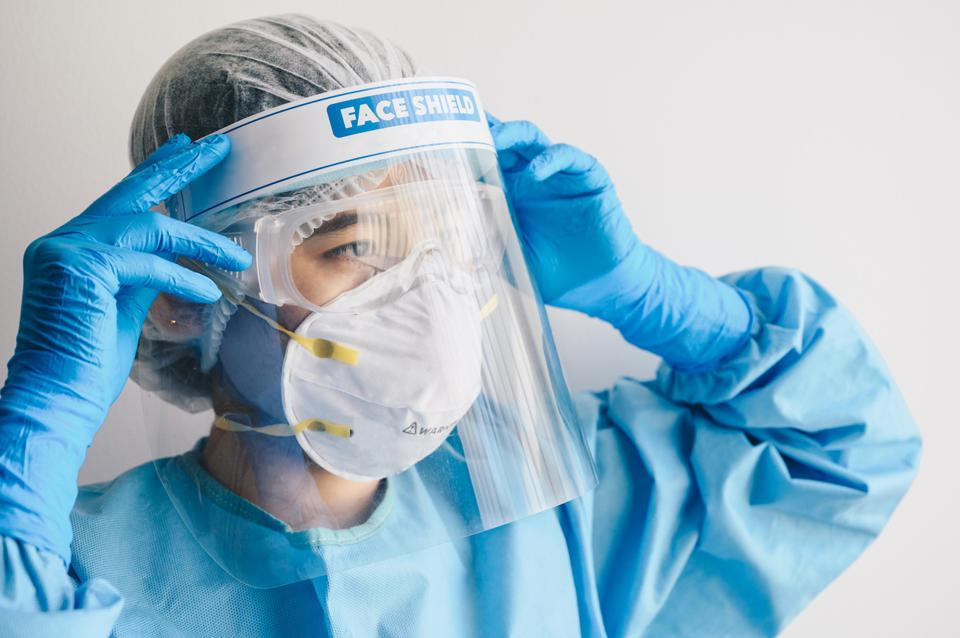 Nurse wearing PPE suit and face shield before working in hospital.