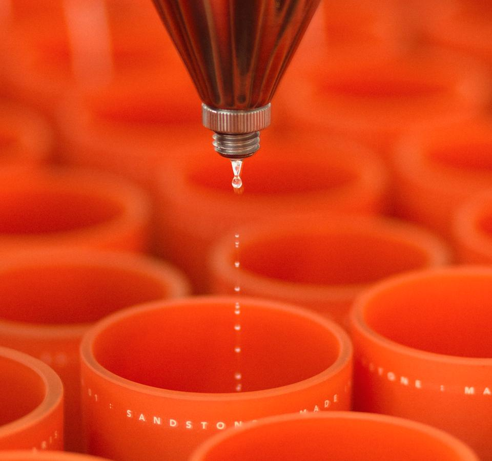 candle vessels in orange being poured with wax