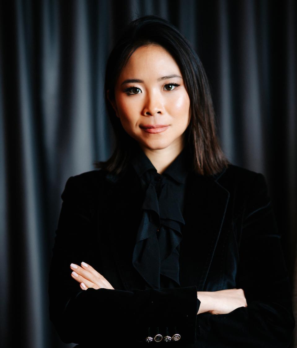 asian woman wearing black suit facing the camera