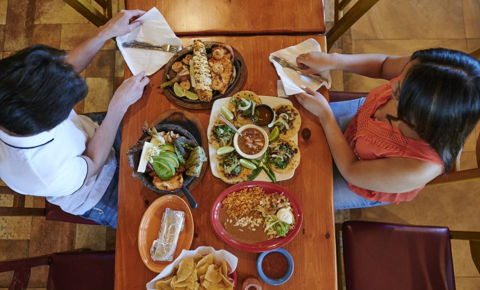 couple seated at a table with tacos and mexican food