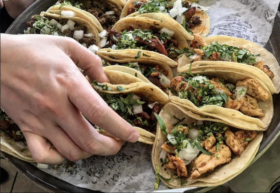hand reaching for tacos on a platter