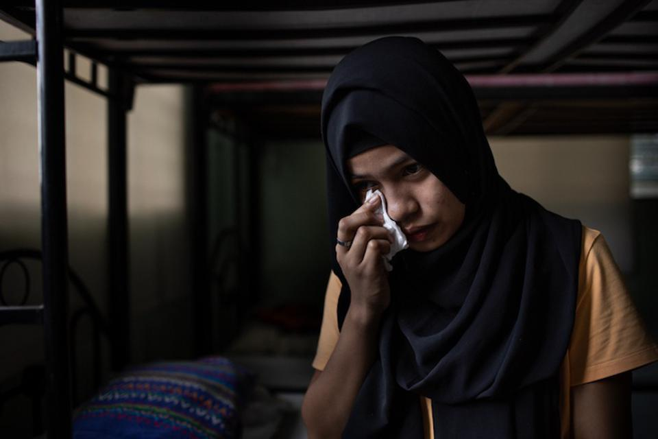 A girl wipes a tear from her eye, telling her story about being tricked into domestic slavery by an unscrupulous employment agency in The Philippines.