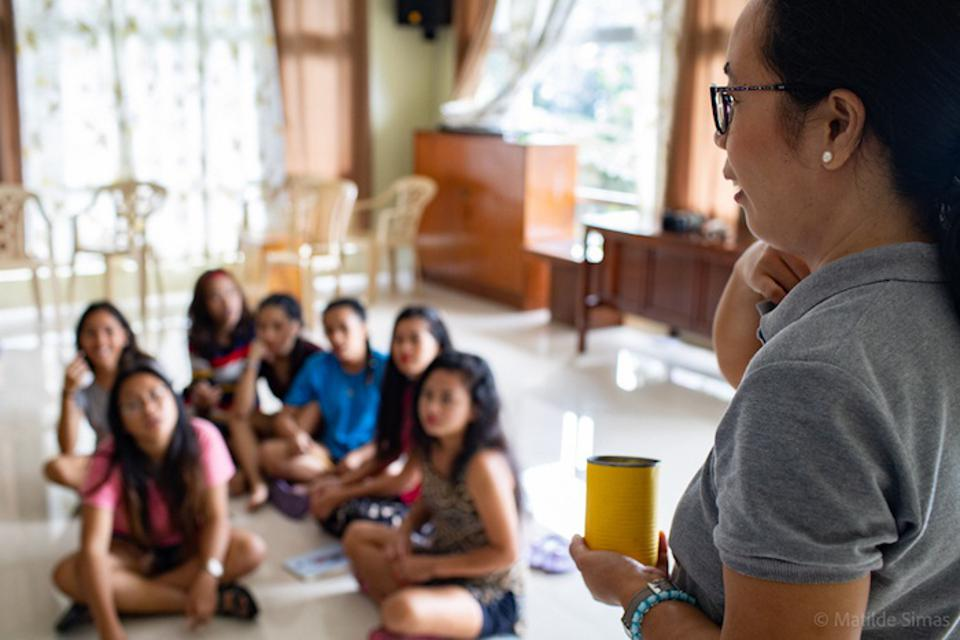 Teenage trafficking victims gather for a peer counseling session with a psychologist.