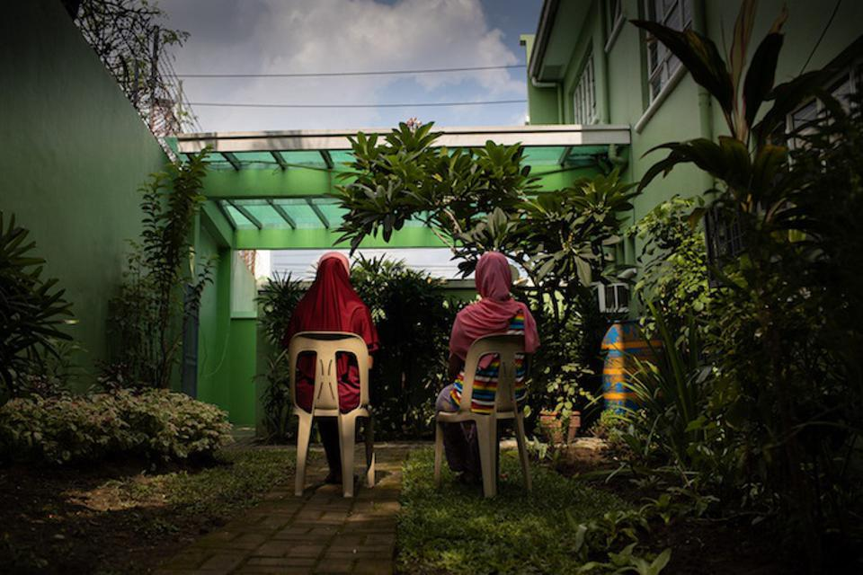 Two girls sitting in plastic chairs are seen from the back in Manila, The Philippines.