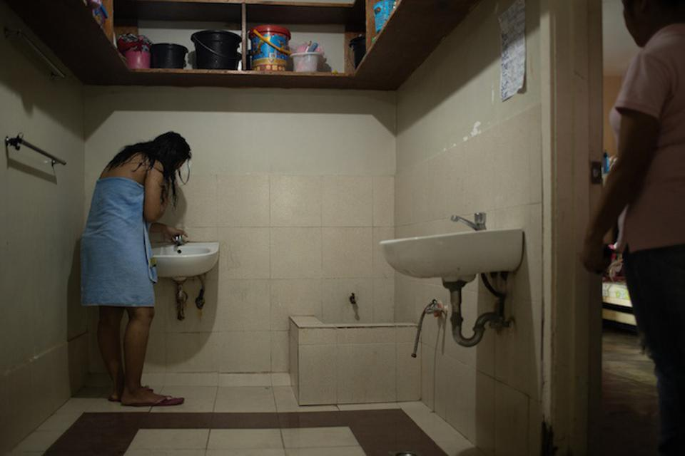 At the shelter, a girl brushes her teeth.