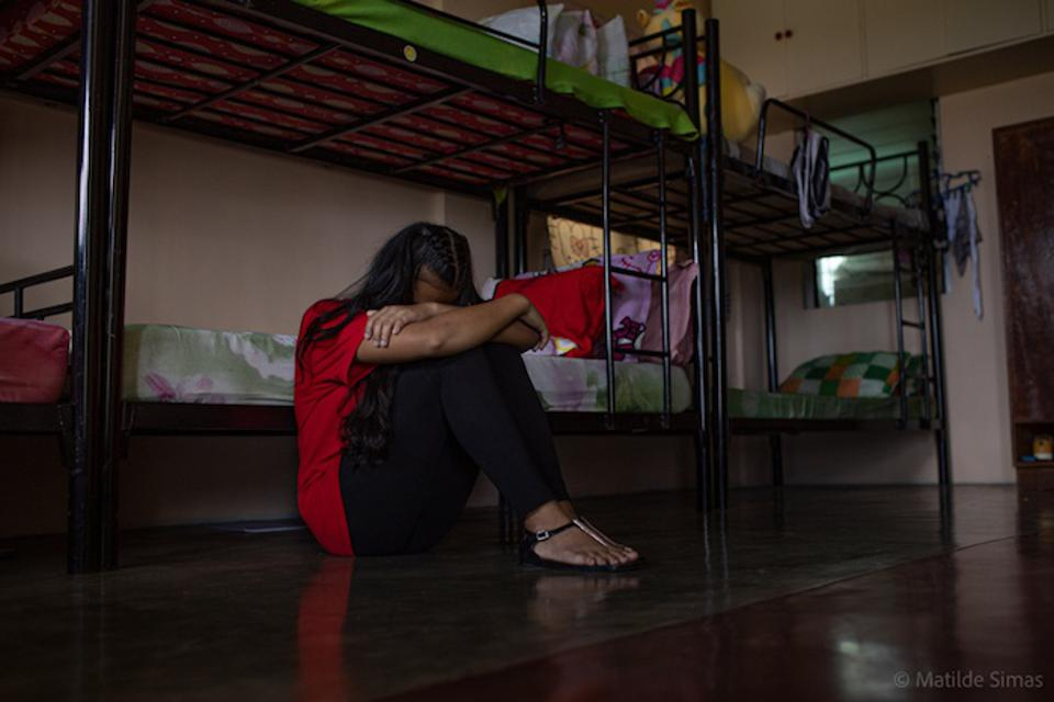 A trafficking survivor puts her head in her arms at a shelter in the Philippines.