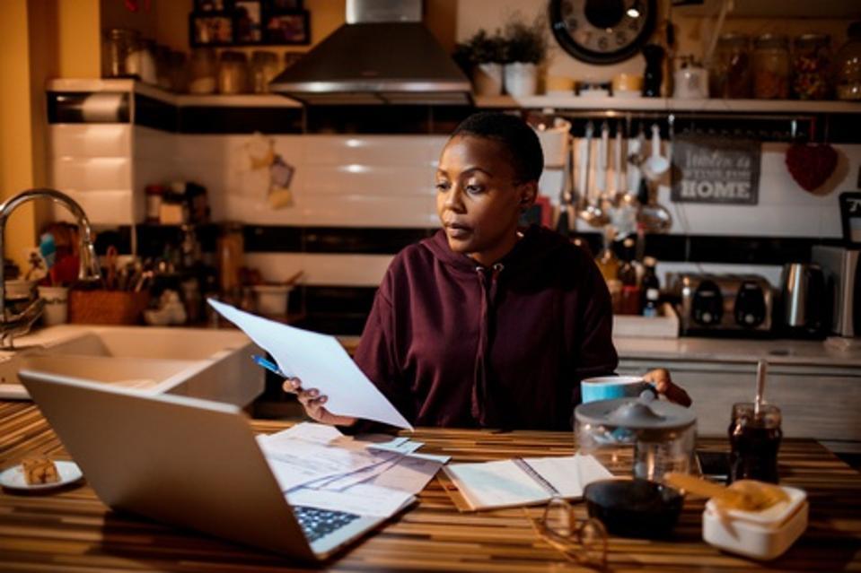 Jeune femme faisant les finances de la maison dans la soirée