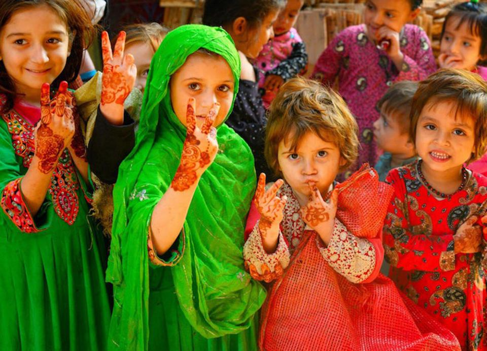 In Lahore, Pakistan, girls between the ages of 3 and 5 welcome a team of polio vaccinators.
