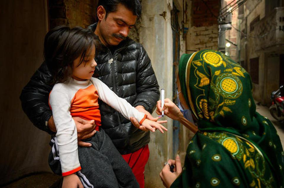 In Lahore, Pakistan, a polio worker marks a child's finger to show they have been vaccinated.