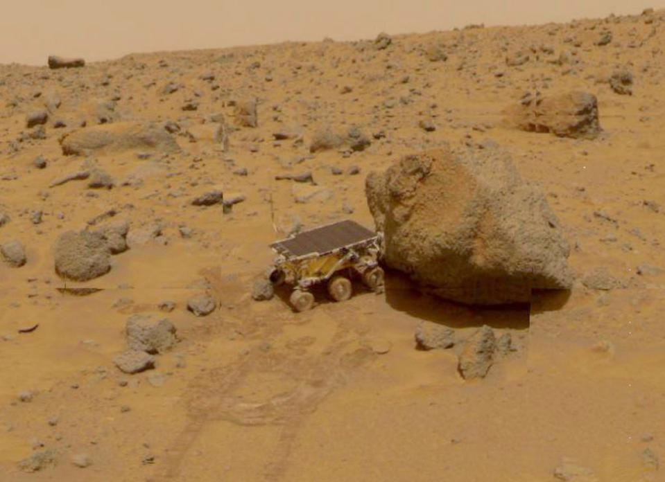 View of the NASA Pathfinder Sojourner Rover exploring the surface terrain of Mars.