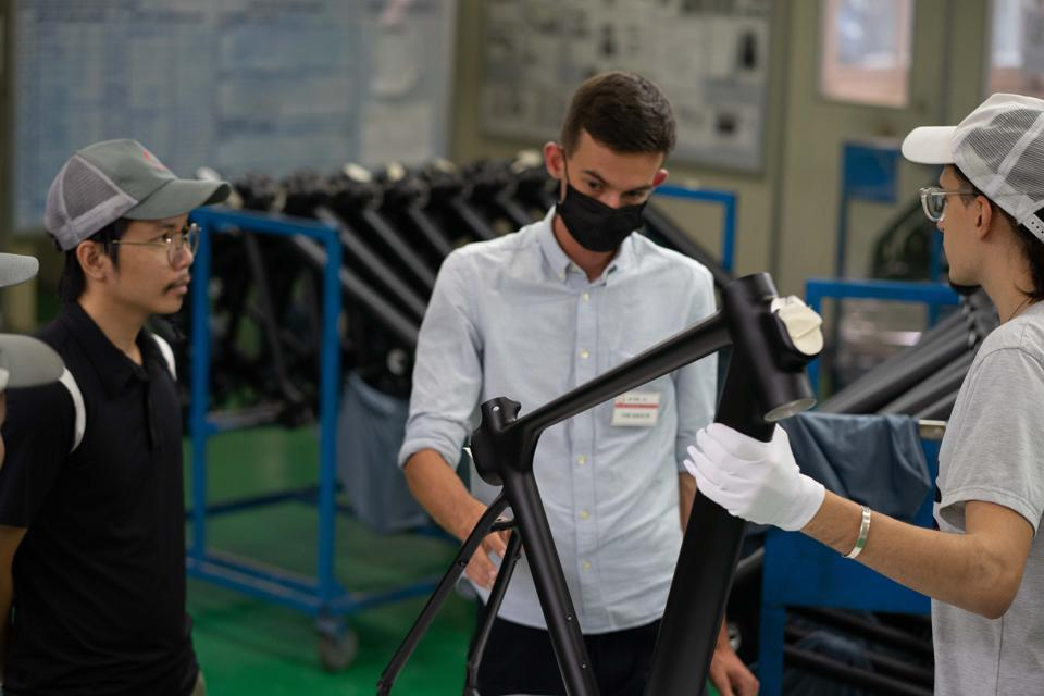 Three men examine electric bicycle frames in a factory in Vietnam.
