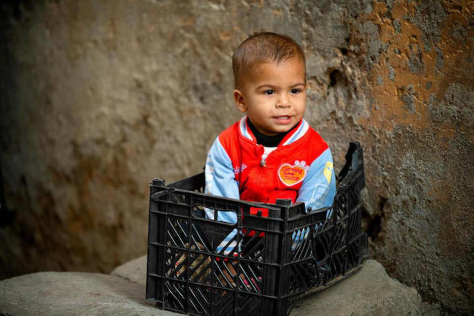 A little boy sits in a plastic crate, waiting for his turn to be vaccinated in Lahore, Pakistan.