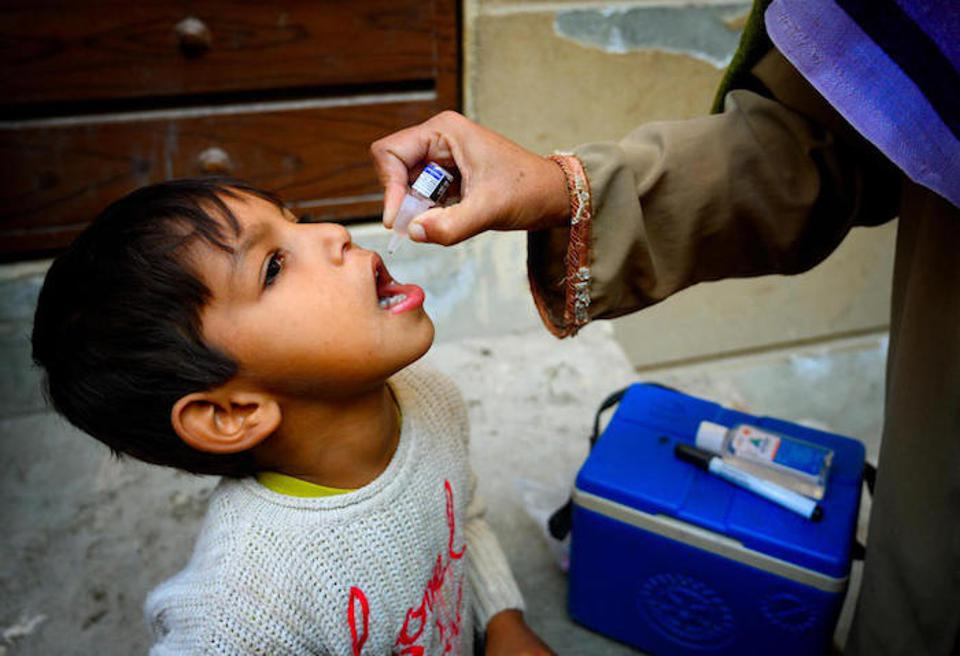 Shumaila, a UNICEF-trained polio vaccinator, gives the vaccine to a 5-year-old boy outside his house in Lahore.