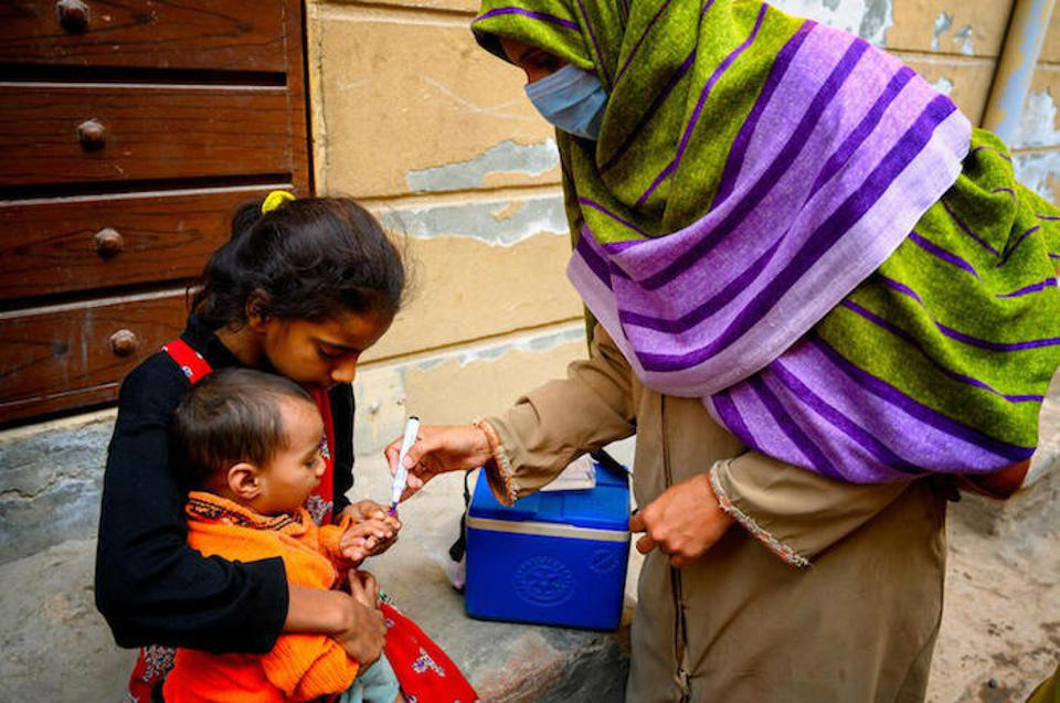 After she has vaccinated a child, Shumaila uses a pen to mark their finger to show they are now safe from polio.