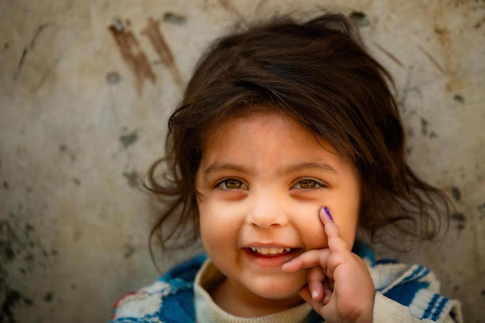 In Lahore, Pakistan, a 3-year-old girl shows her finger, marked purple to show she is safe from polio.
