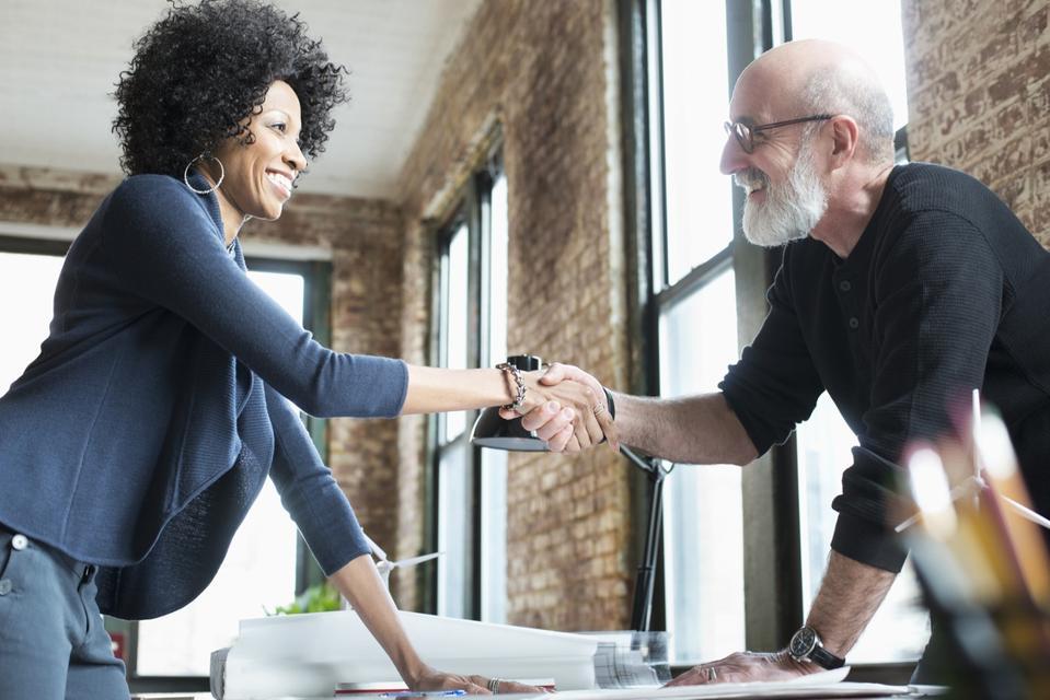 Business people handshaking over blueprints on desk