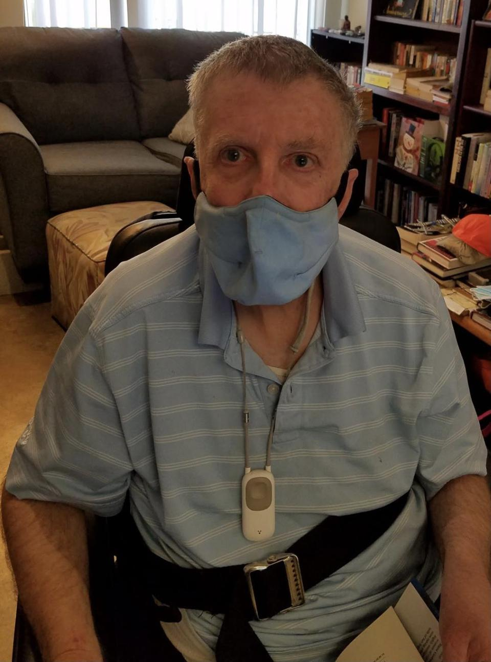 A white older man wearing a light blue face mask.