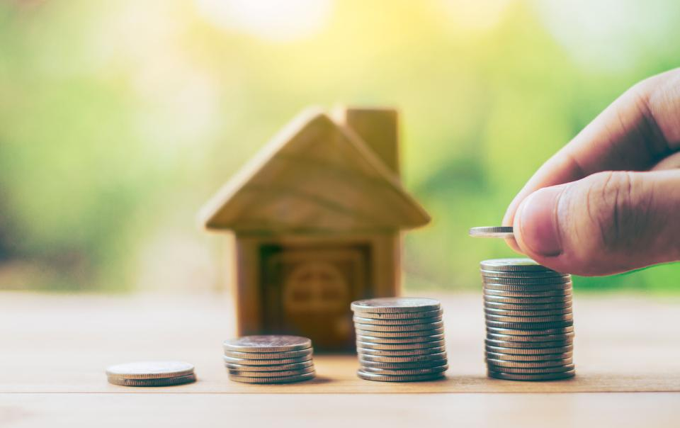 Coins and house on the wood is ladder. Men's hand is putting coins. planning savings money of coins to buy a home concept for property ladder,