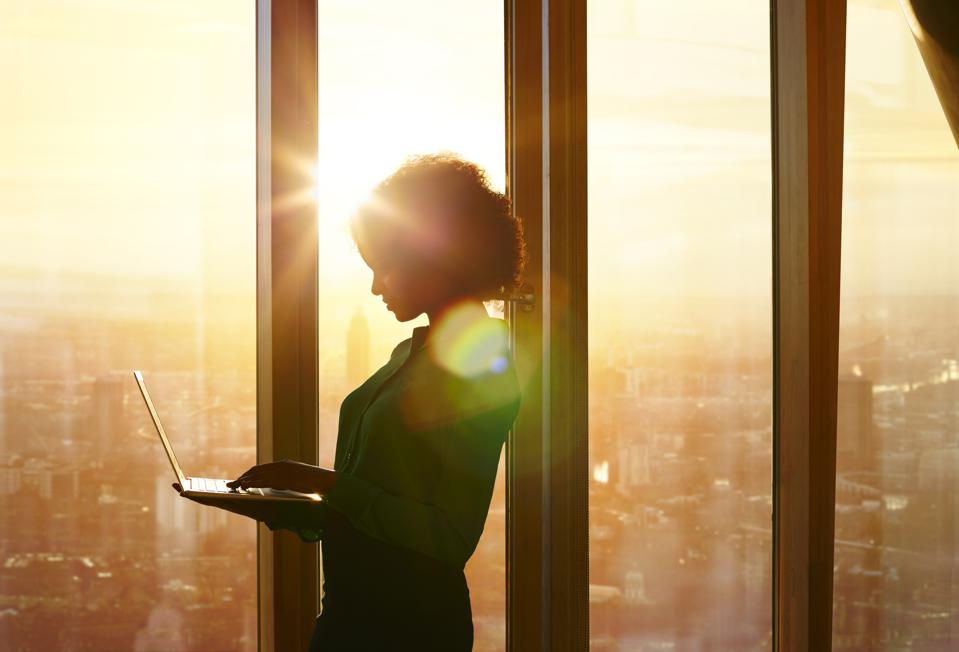 Businesswoman on laptop at window in morning sun