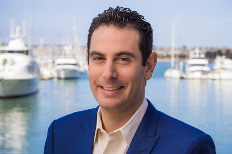 Adam Beer, GM, Lido House, an Autograph Collection property, pictured in front of the Newport Beach marina with yachts and sailboats in the background