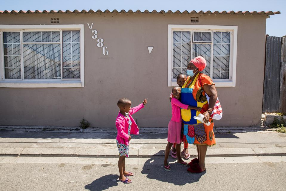 Elda Sidlabane (66 years old) is greeted by her new adopted grandchildren as she arrives home from her seniors group meeting outside Cape Town, South Africa in February 2021