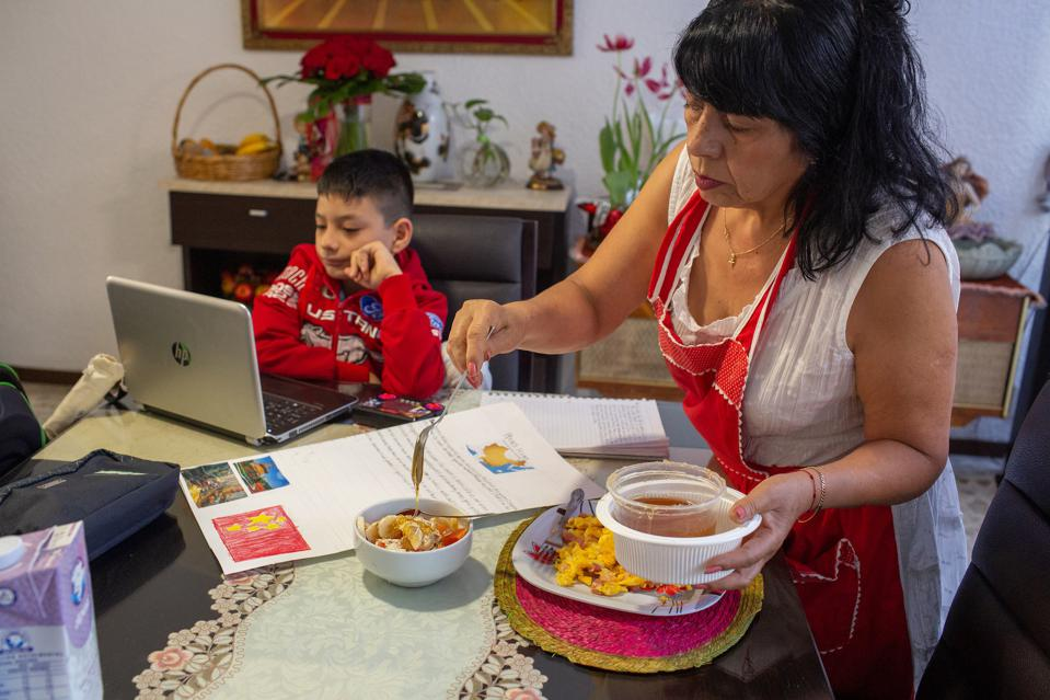 Alicia Ruiz Robles, 65, serves breakfast to her two young grandsons in her Mexico City home in February 2021. The boys are attending school online