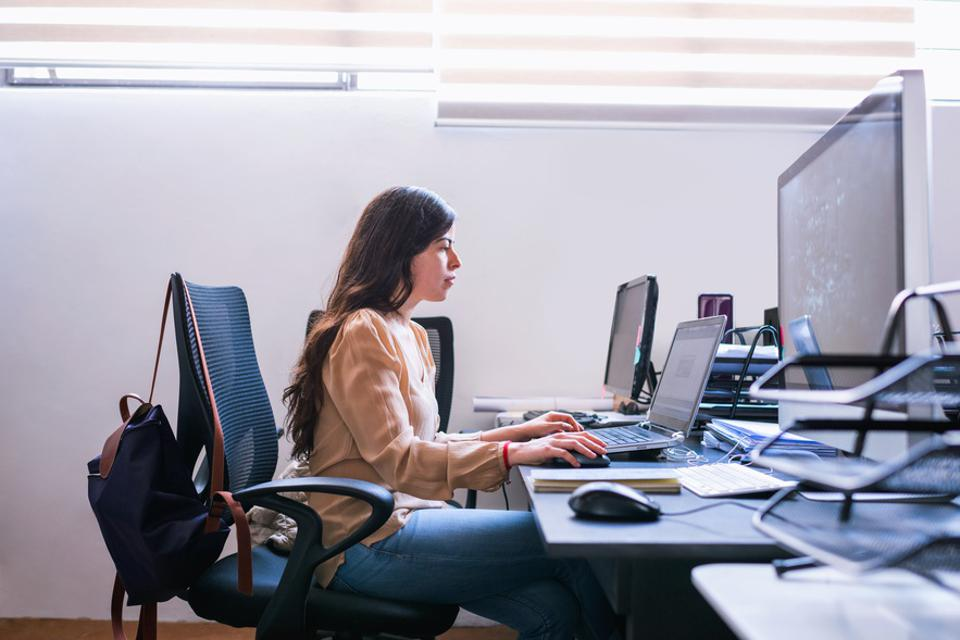 Young woman architect working on computer in office