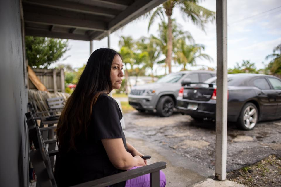 Woman sits on porch in front of cars parked on driveway