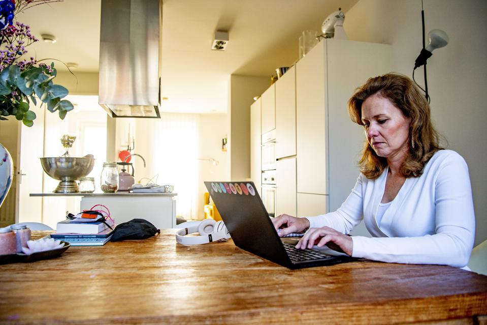 A woman working from home as a preventive measure against...
