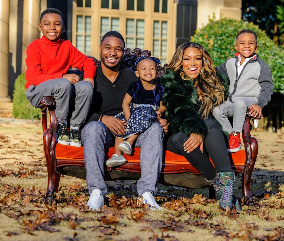 Ralph Pittman, Jr, his wife Drew Sidora, and their three children sitting on a bench outside.