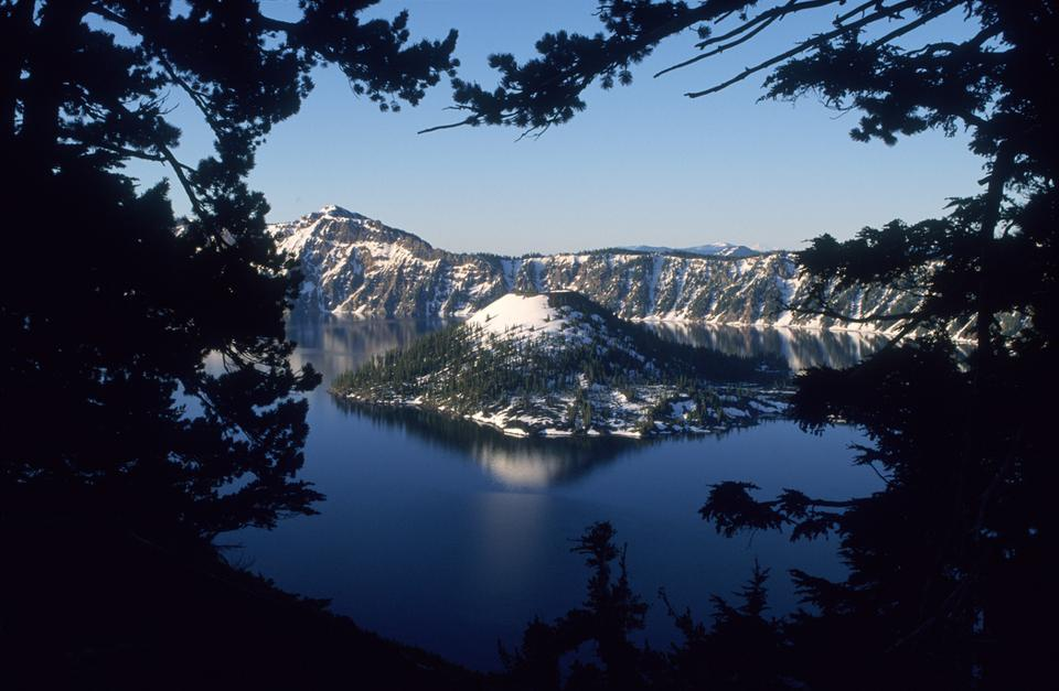 Crater Lake National Park with snow capped glaciers in distance as a deep blue lake on foreground.