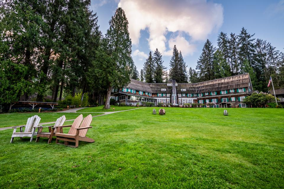 The exterior of Lake Quinault Lodge with Adirondack chairs in foreground on a green lawn.