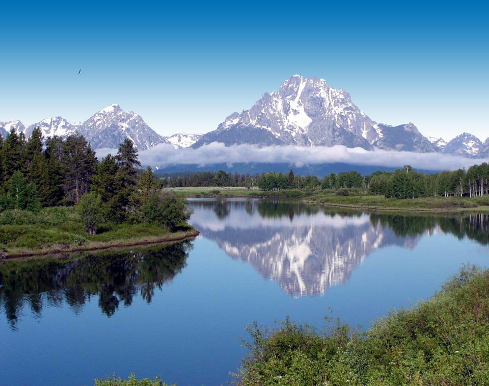 A mirror-perfect view of snow capped mountains through the pristine lake at Bridger-Teton National Forest