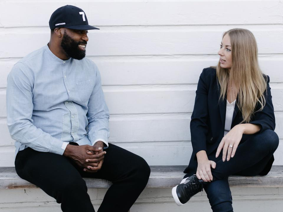 Davis and Yudina sit on a bench against a white wall