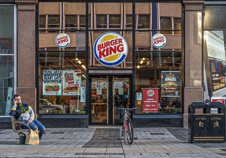 A customer sits outside Burger King fast food store...
