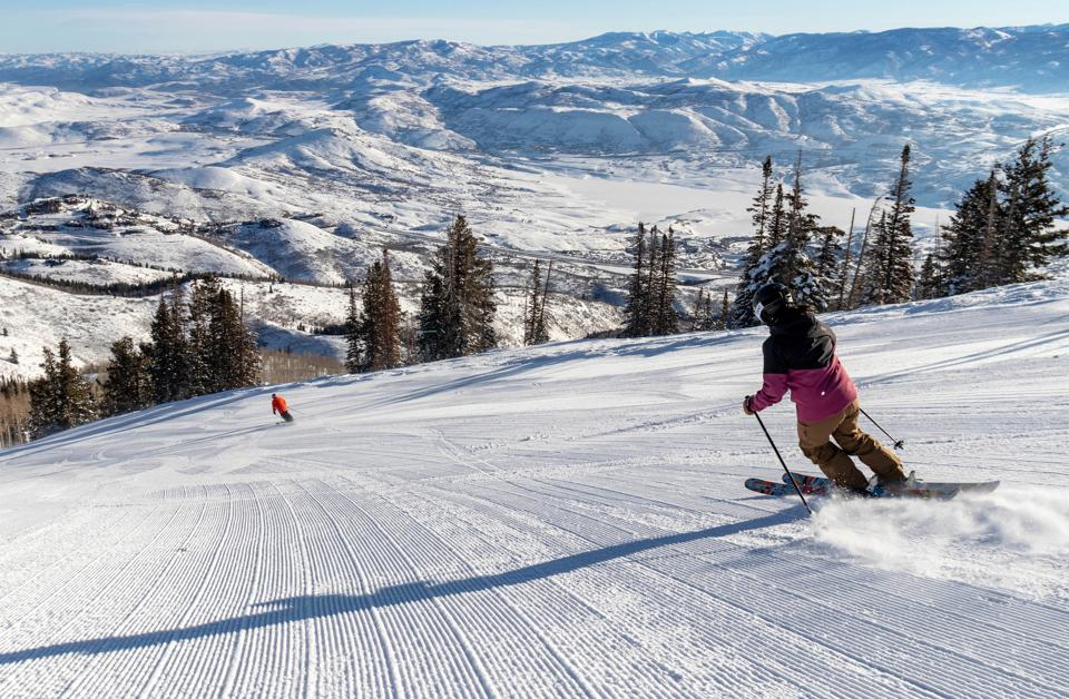 Two skiers coming down a groomed slope at Deer Valley.