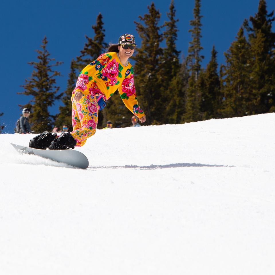 A woman snowboarder having fun at Aspen.