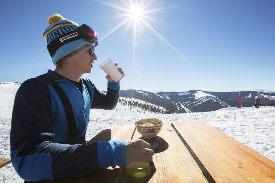 A skier at a picnic table drinking coffee at Vail.