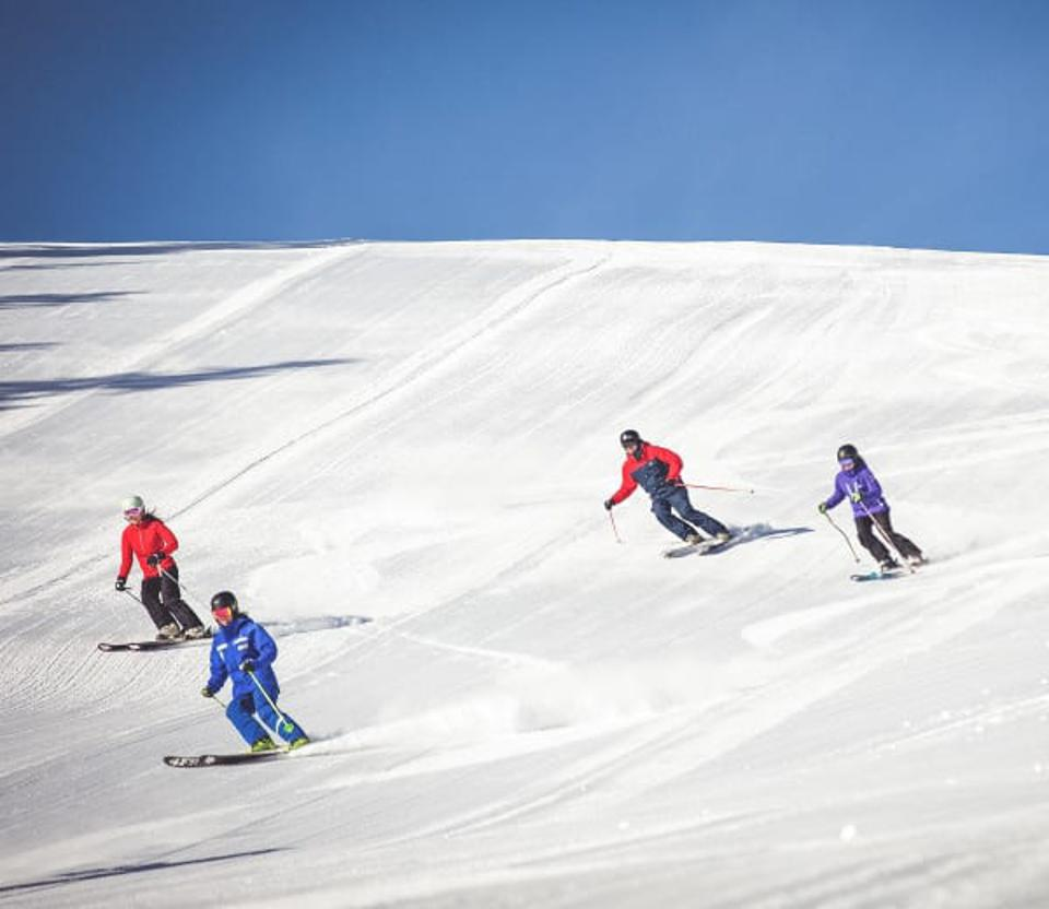 Four skiers coming down a wide slope at Northstar.