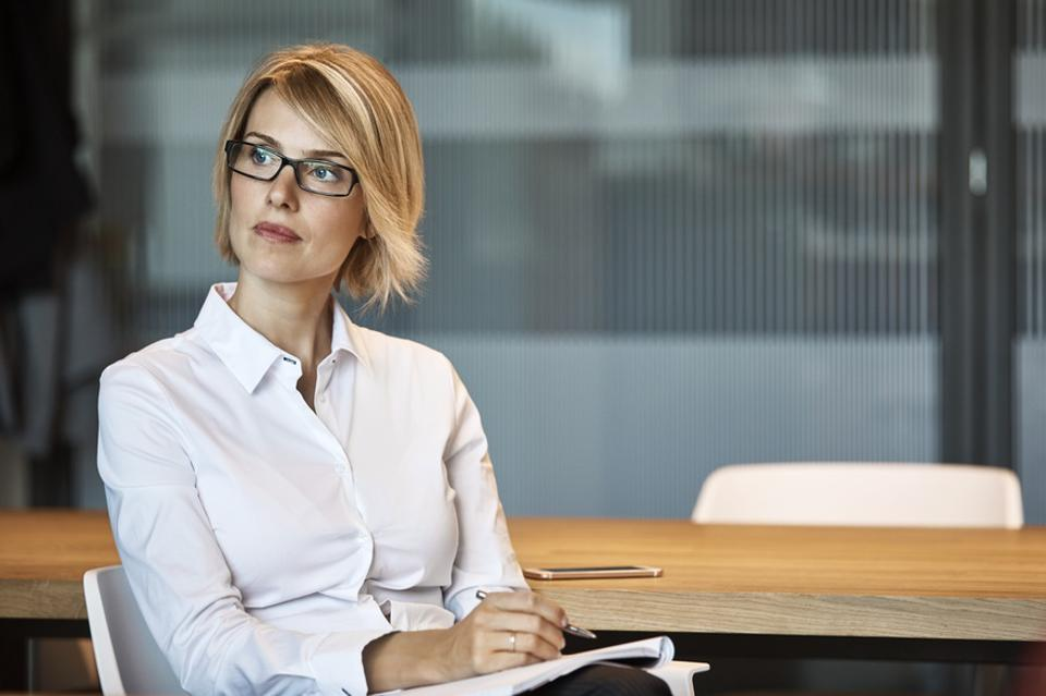 Thoughtful businesswoman looking away at desk