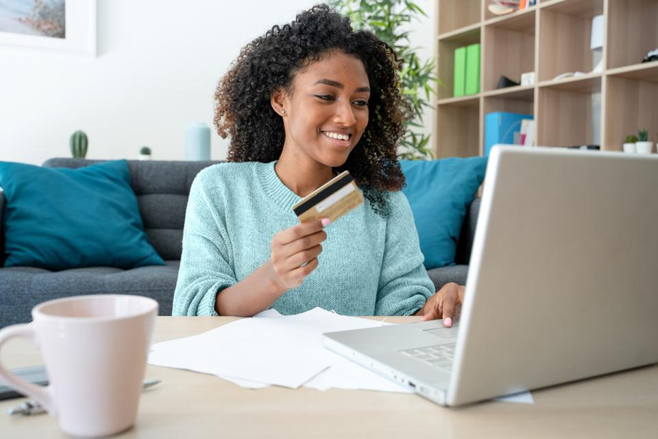 Black woman using credit card for online shopping