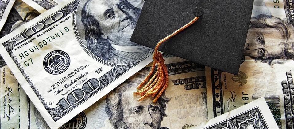 Dollar bills and graduation cap
