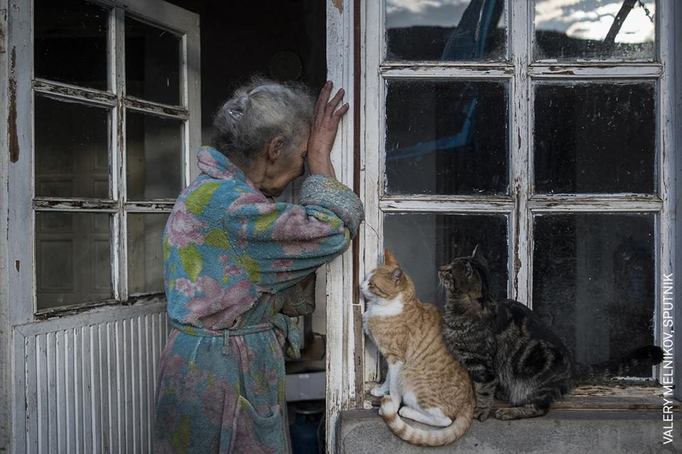 World Press Photo contest: an old woman crying at the door of her bombarded home.