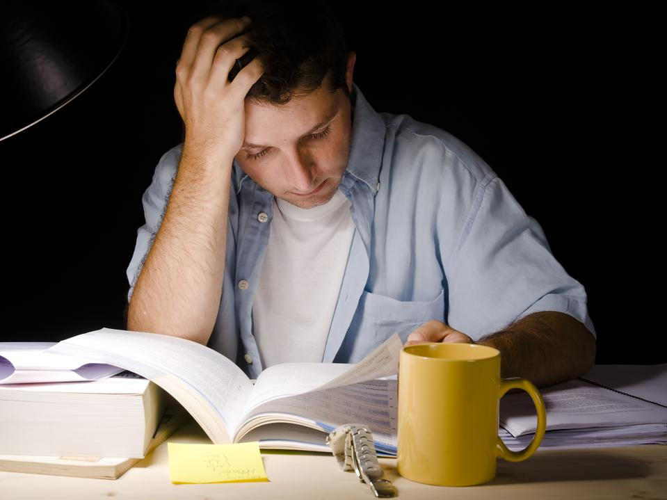 Student studying at night with a desk lamp on