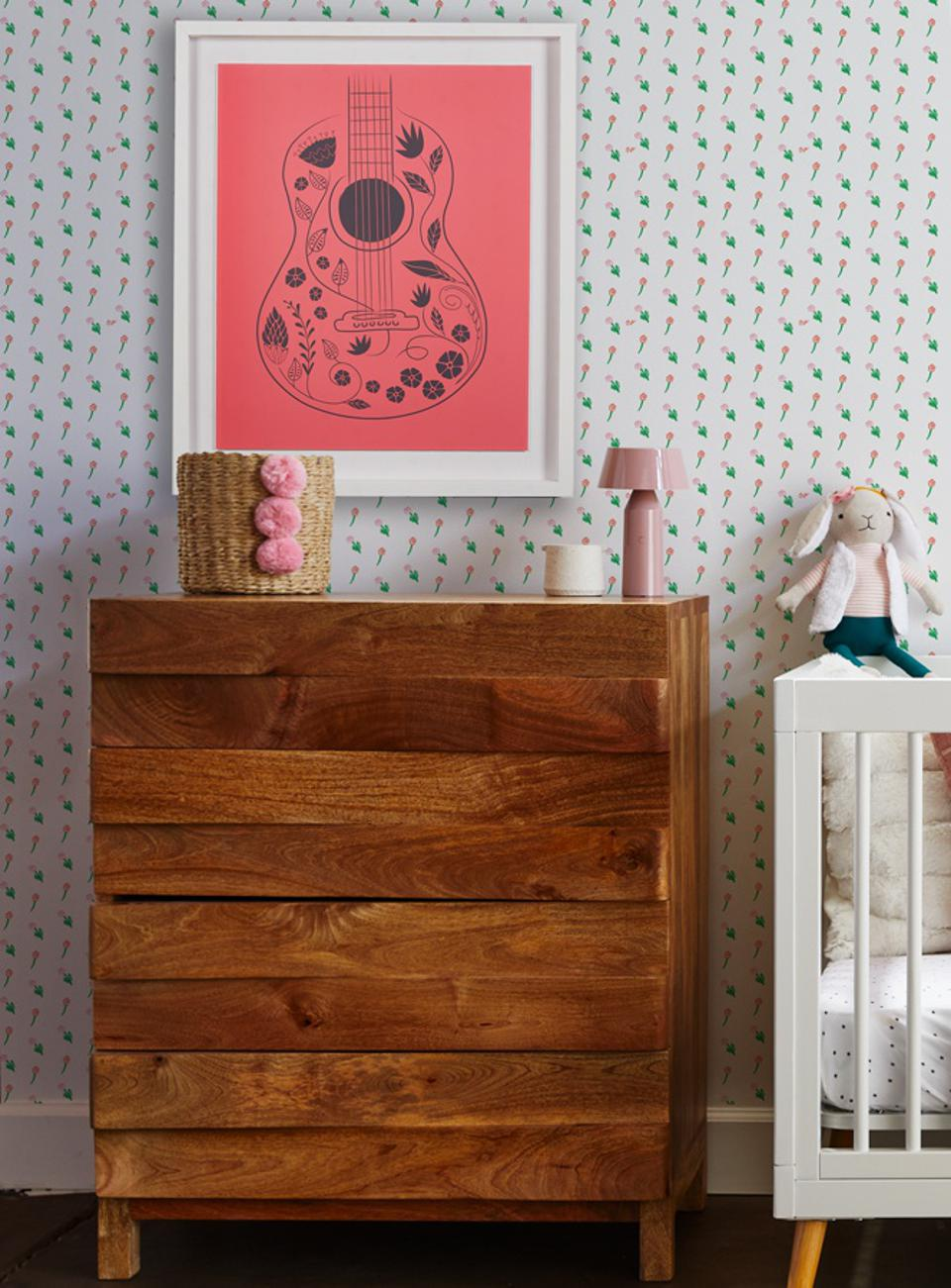 Framed art print of a pink guitar on wall in baby's room near crib