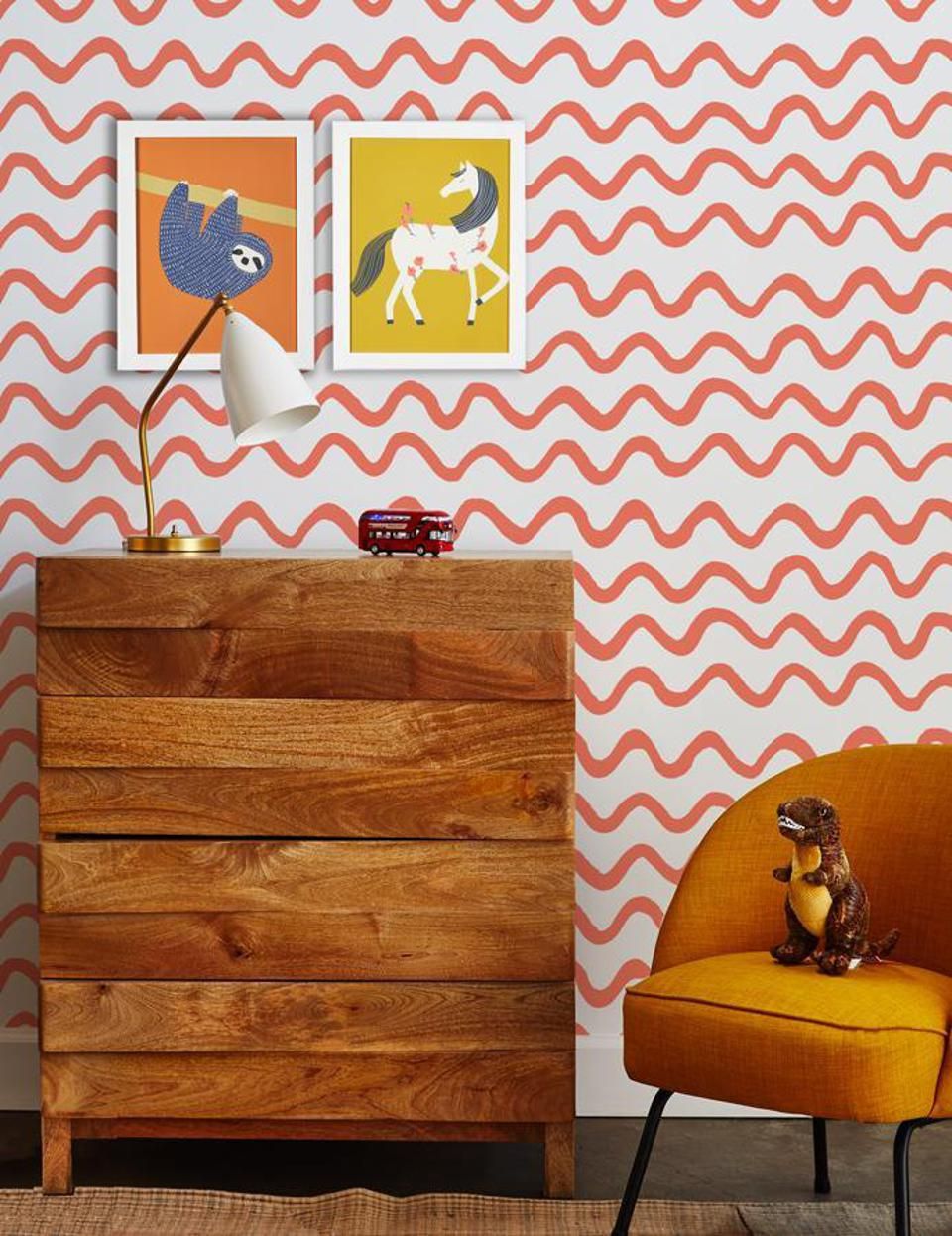 sloth and pony art prints on wall with orange squiggly line wallpaper in kids room
