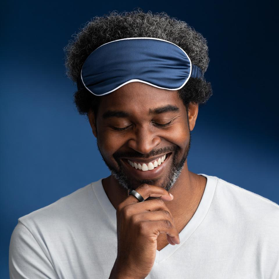 A man smiles wearing an Oura smart ring with a blue sleep mask in a white tshirt.
