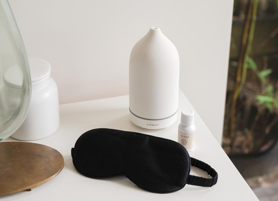 A Vitruvi diffuser, black silk sleep mask and bottle of the sleep blend on a white table.